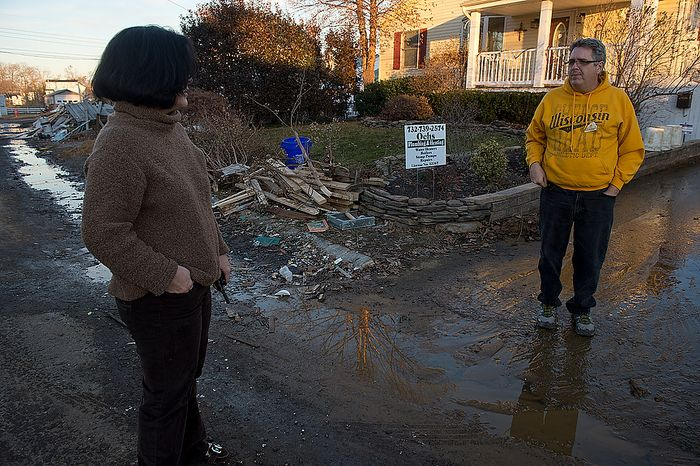 Mom Tiffany talks with Frank Wells in Union Beach, N.J. on Wednesday, Nov. 21, 2012. He says his side of the street was lucky. The Audas family has donated items here that they collected in Project Keep Them Cozy, which Abbi, 12, and Andrew, 9, spearheaded. The family is spending their Thanksgiving up here volunteering. (Barbara L. Salisbury/The Washington Times)