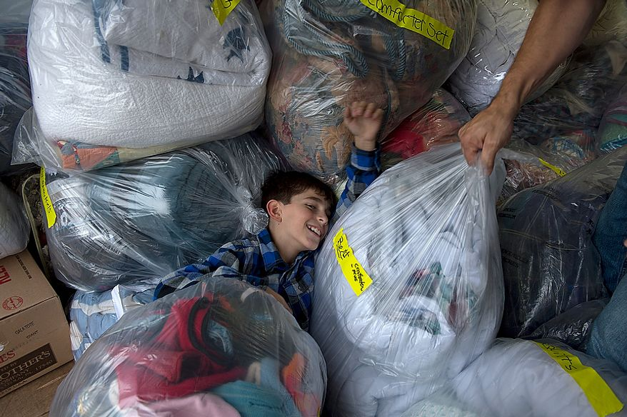 """I'm sinking!"" says Andrew Audas, 9, as he falls back into a pile of bags full of donated bedding inside the 12-foot rental truck that he and his family are filling Tuesday, Nov. 20, 2012 at their Bethesda, Md. home to take up to New Jersey for Hurricane Sandy victims. Andrew and his sister Abbi decided to collect things for victims of Hurricane Sandy. Their project, called ""Keep Them Cozy,"" has collected enough donations to fill this truck. The family will drive everything up to New Jersey on Wednesday, and they will spend Thanksgiving and the weekend volunteering up there. (Barbara L. Salisbury/The Washington Times)"