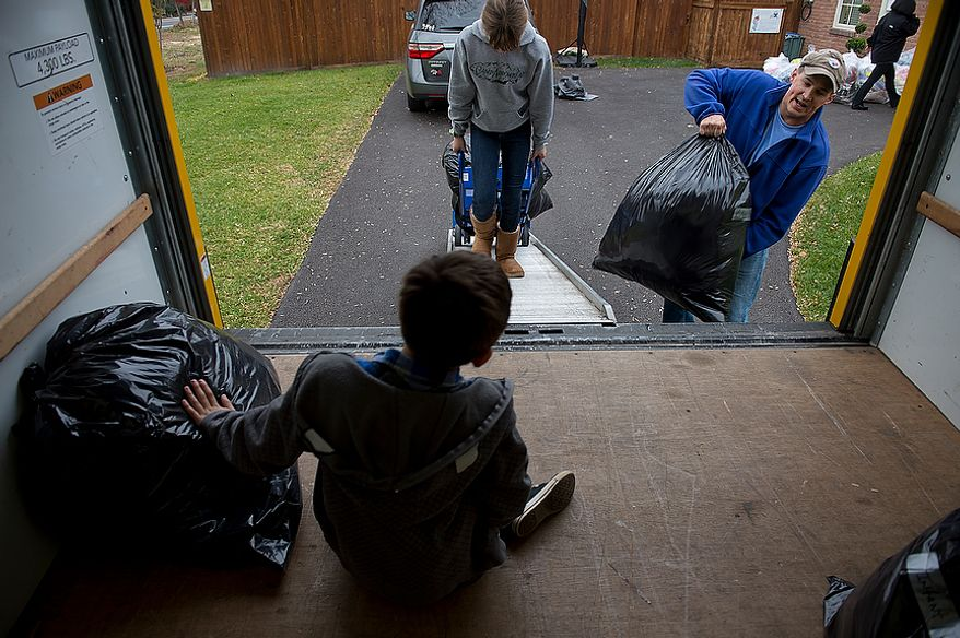 Andrew Audas, 9, bottom, sits inside the rented truck while his sister Abbi, 12, and dad Jim load bags and mom Tiffany, right, heads to the garage to pull out more stuff. The family filled their 12-foot rental truck with donations for victims of Hurricane Sandy on Tuesday, Nov. 20, 2012. They leave Wednesday morning to drive everything up to New Jersey, where they will spend Thanksgiving and the weekend volunteering. (Barbara L. Salisbury/The Washington Times)