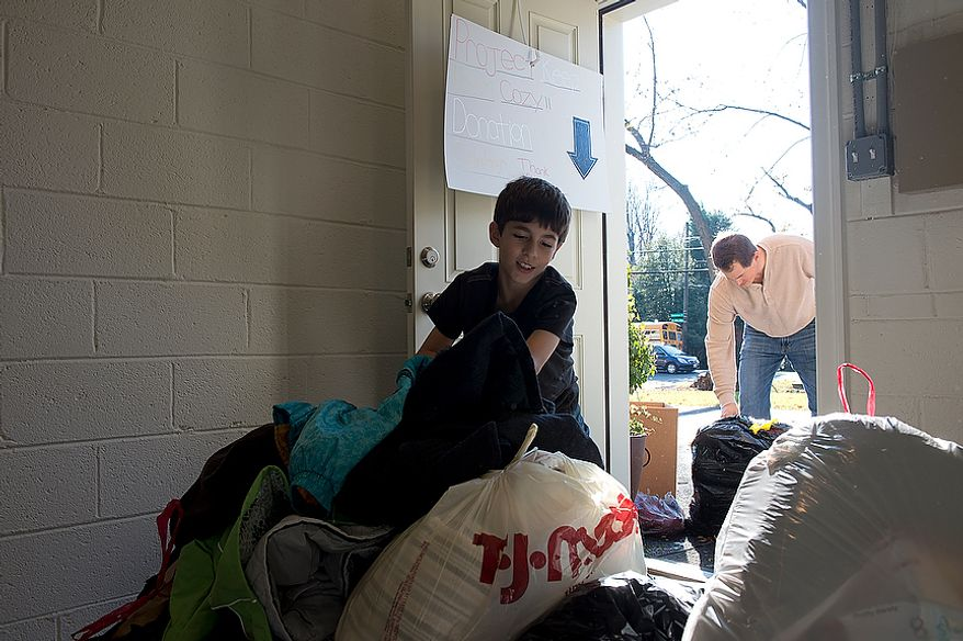 "Nine-year-old Andrew Audas carries newly donated bags into the basement of his Bethesda, Md. home while his dad, Jim, gets more bags from outside. Their house has become the home base for the family's ""Project Keep Them Cozy."" The Audas children were struck by the devastation caused by Hurricane Sandy and told their parents they wanted to do something to help. So they created ""Project Keep Them Cozy"" and asked friends, schoolmates and neighbors to donate hats, gloves, coats and scarves. They have received all kinds of clothing, blankets and bedding, which they will drive up to New Jersey. They plan to stay up there through the Thanksgiving holiday to volunteer. This image was made Tuesday, Nov. 13, 2012. (Barbara L. Salisbury/The Washington Times)"