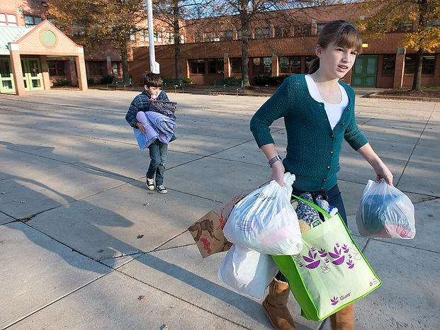"Abbi Audas, right, 12, and her brother Andrew, 9, carry donated items out of Abbi's school, Pyle Middle School in Bethesda, Md., on Wednesday, Nov. 14, 2012. The Audas children placed donation boxes at each of their schools for ""Project Keep Them Cozy,"" asking people to donate items for Hurricane Sandy victims. The family will drive all of the donated items to New Jersey on Wednesday and then stay through the Thanksgiving holiday to volunteer. (Barbara L. Salisbury/The Washington Times)"