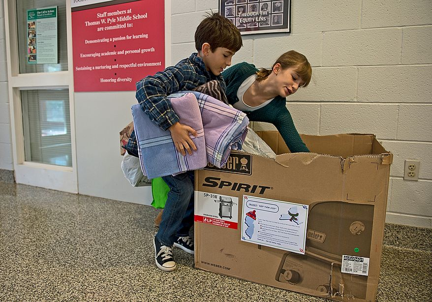 On Wednesday, Nov. 14, 2012, Abbi and Andrew Audas pick up donations from the Keep Them Cozy box at Abbie's school, Pyle Middle School in Bethesda, Md. The family regularly checks the boxes at both children's schools, and they keep getting donations dropped off at their house as well. They plan to leave next Wednesday to drive things up to New Jersey, where they will stay and volunteer for a few days. (Barbara L. Salisbury/The Washington Times)