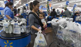 Consumer Eva Cevallos with her eleven-month daughter, Quinn, shop for Thanksgiving celebrations at the Pre-Black Friday event at the Walmart Supercenter store in Rosemead, Calif., Wednesday, Nov. 21, 2012. (AP Photo/Damian Dovarganes)