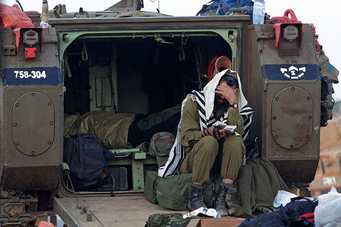 An Israeli soldier prays as he sits at an armored personnel carrier at a staging area near the Israel Gaza Strip Border, southern Israel, Wednesday, Nov. 21, 2012. The Israeli military has been pounding Gaza with at least 30 strikes overnight, hitting government ministries, smuggling tunnels, a banker's empty villa and a Hamas-linked media office. Meanwhile, U.S. Secretary of State Hillary Clinton is in the West Bank, trying to help negotiate a truce between Israel and the militant Hamas, which controls the Gaza Strip. (AP Photo/Lefteris Pitarakis)