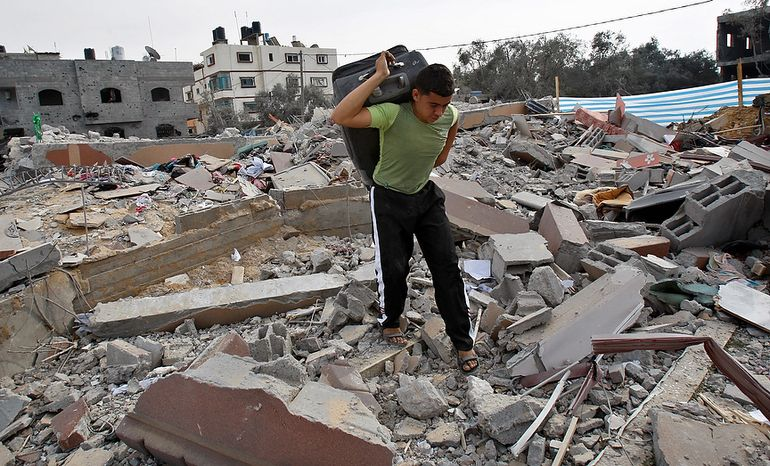 A Palestinian walks through rubble of the house of Issam Al Da'slees, top aide of Hamas Prime Minister Ismail Haniyeh, after it  was hit by an Israeli air strike in Nuseirat Refugee Camp, central Gaza Strip, Wednesday, Nov. 21, 2012. (AP Photo/Adel Hana)