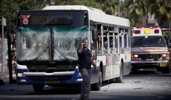 An Israeli security officer stands next to a blown-up bus at the site of a bombing in Tel Aviv on Nov. 21, 2012. The bomb ripped through the bus near the nation's military headquarters, wounding several people, Israeli officials said. The blast came amid a weeklong Israeli offensive against Palestinian militants in Gaza. (Associated Press)