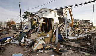 Backhoe operator Keith Henry levels a storm-damaged home in the Breezy Point section of the Queens borough of New York, Tuesday, Nov. 20, 2012. (AP Photo/Mark Lennihan)