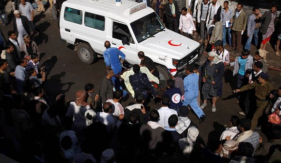 Yemeni medics and soldiers carry a body of a soldier at the site a plane crash in Sanaa, Yemen, Wednesday, Nov. 21, 2012. Yemeni security officials say a military plane has crashed during training over the capital, Sanaa, killing all 10 people on board. (AP Photo/Hani Mohammed)