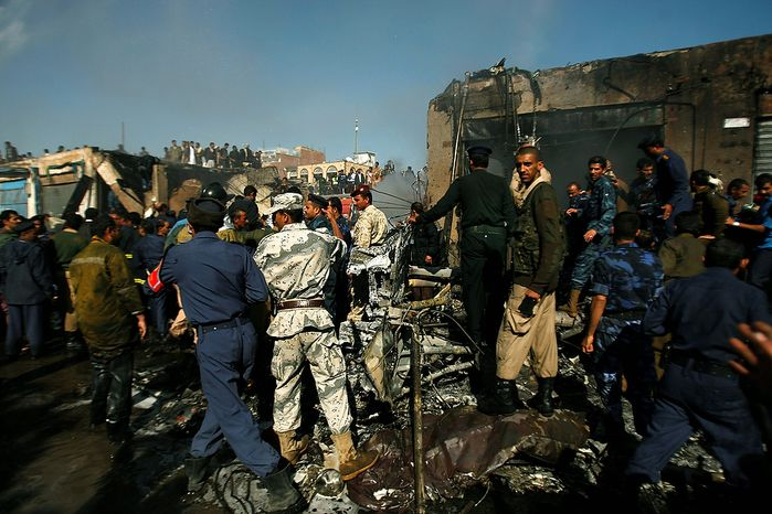 Army and police officers work at the scene of a plane crash in Sanaa, Yemen, Wednesday, Nov. 21, 2012. Yemeni security officials said the military plane crashed during training over the capital, Sanaa, killing all 10 people on board. (AP Photo/Hani Mohammed)
