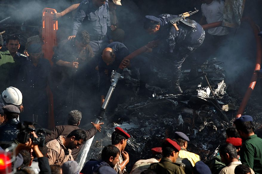 Army and police officers work at the scene of a plane crash in Sanaa, Yemen, Wednesday, Nov. 21, 2012. Yemeni security officials say a military plane has crashed during training over the capital, Sanaa, killing all 10 people on board. (AP Photo/Hani Mohammed)