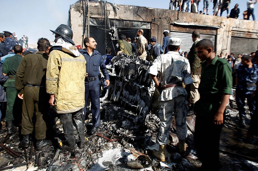 Army and police officers gather at the scene of a plane crash in Sanaa, Yemen, Wednesday, Nov. 21, 2012. Yemeni security officials say a military plane has crashed during training over the capital, Sanaa, killing all 10 people on board. (AP Photo/Hani Mohammed)