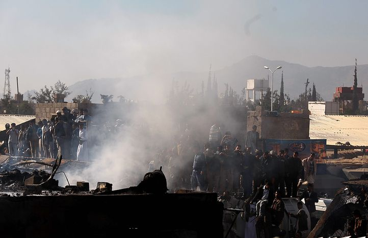 Yemeni people gather at the site of a plane crash in Sanaa, Yemen, Wednesday, Nov. 21, 2012. Yemeni security officials say a military plane has crashed during training over the capital, Sanaa, killing all 10 people on board. (AP Photo/Hani Mohammed)