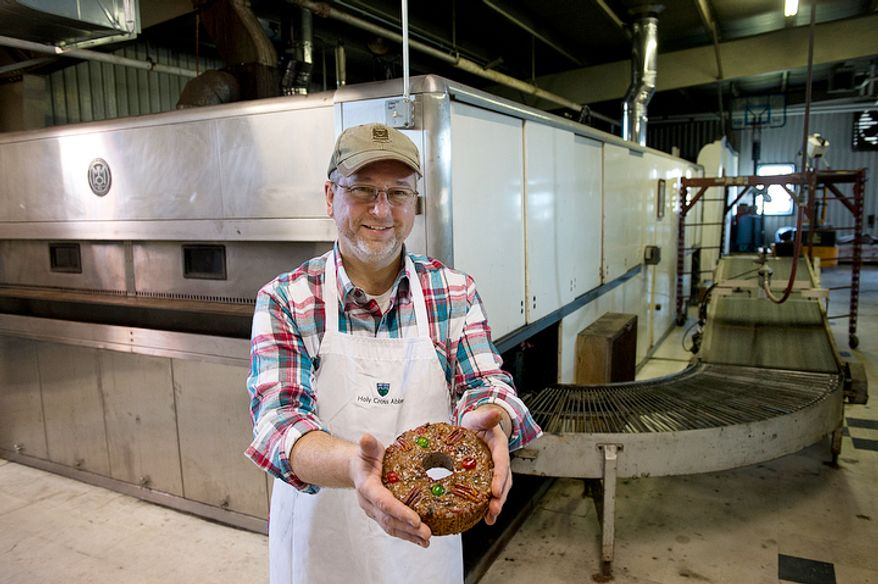 Ernie Polanskas, bakery manager at the Holy Cross Abbey bakery in Berryville, Va., holds one of the famous fruitcakes made by the monks in front of the huge industrial-sized oven that they bought back in the 1960s to bake bread. The monks bake from January to September, making about 10,000 fruitcakes, which they ship all over the world, primarily during the holiday season. The proceeds from the sales go to support the day-to-day operations of the monastery. This image was made Tuesday, Nov. 13, 2012. (Barbara L. Salisbury/The Washington Times)