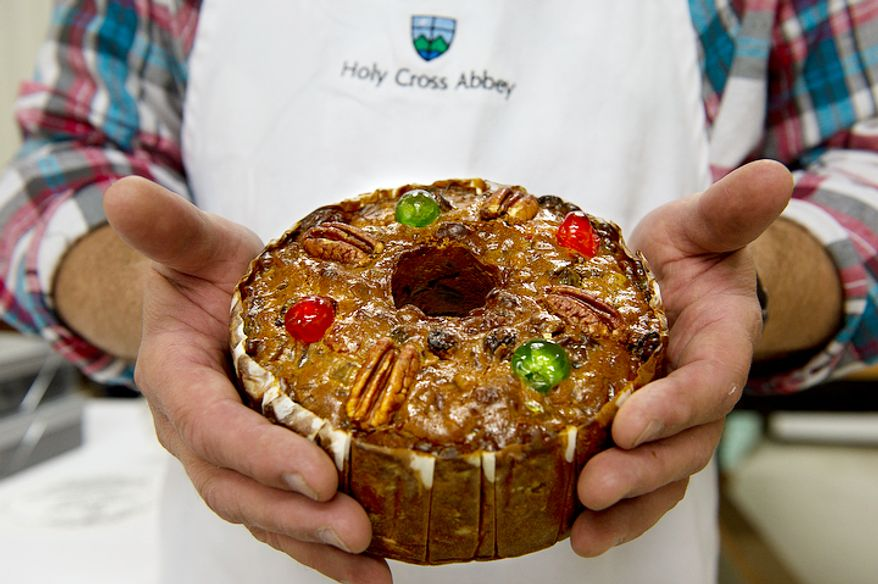 Ernie Polanskas, bakery manager at the Holy Cross Abbey bakery in Berryville, Va., holds one of the famous fruitcakes made by the monks on Tuesday, Nov. 13, 2012. He says that they use a recipe that they got from Betty Crocker back in the 1960s which they have tweaked a little over the years. Their fruitcake is two-thirds candied fruits and nuts, and he says this fact, along with the fact that they steam it while they bake it, keeps it really moist.  (Barbara L. Salisbury/The Washington Times)