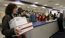 **FILE** People wait in line at the U.S. Postal Service Airport station in Los Angeles on Dec. 19, 2011. (Assocaited Press)