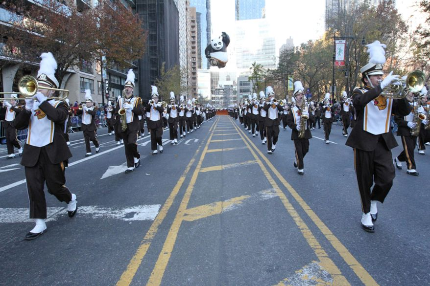 Members of the Kenton Ridge High School Marching Cougar Band, from Springfield, Ohio, make their way along New York's Central Park South as the Kung Fu Panda balloon follows behind them during the 86th Annual Macy's Thanksgiving Day Parade Thursday Nov. 22, 2012, in New York. The annual Macy's Thanksgiving Day Parade put a festive mood in the air in a city still coping with the aftermath of Superstorm Sandy.  (AP Photo/Tina Fineberg)