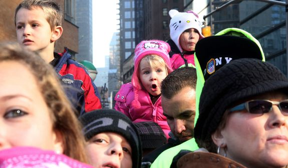 Reagon Long, 3, from Oxford, N.Y, background center, watches the 86th Annual Macy's Thanksgiving Day Parade Thursday Nov. 22, 2012, in New York. The annual Macy's Thanksgiving Day Parade put a festive mood in the air in a city still coping with the aftermath of Superstorm Sandy.  (AP Photo/Tina Fineberg)