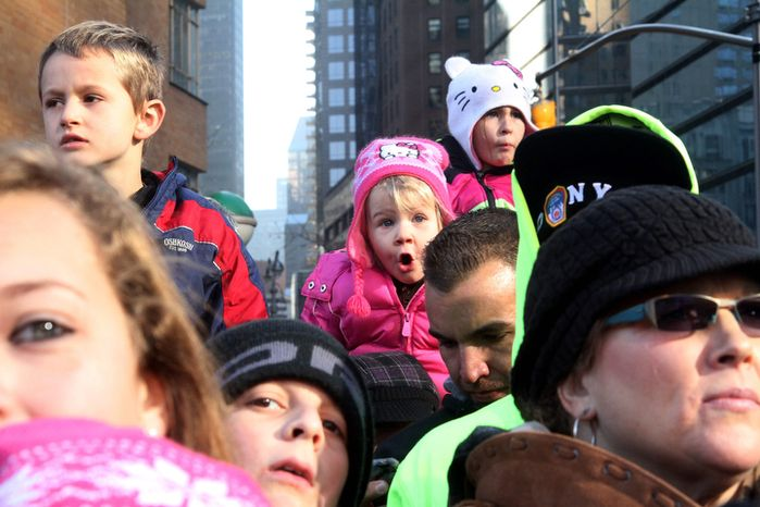 Reagon Long, 3, from Oxford, N.Y, background center, watches the 86th Annual Macy's Thanksgiving Day Parade Thursday Nov. 22, 2012, in New York. The annual Macy's Thanksgiving Day Parade put a festive mood in