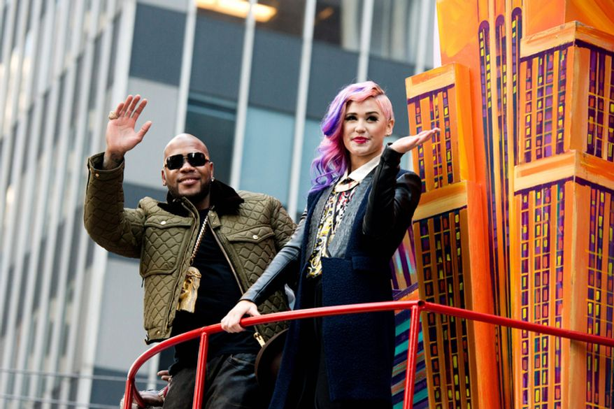 Flo Rida and Stayc Reigns ride a float in the Macy's Thanksgiving Day Parade in New York, Thursday, Nov. 22, 2012. The American harvest holiday came as portions of the Northeast were still coping with the wake of Superstorm Sandy, and volunteers planned to serve thousands of turkey dinners to people it left homeless or struggling. (AP Photo/Charles Sykes)