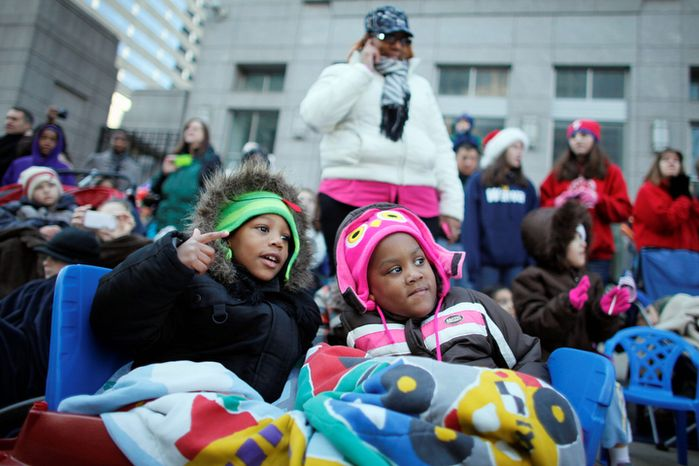 Four year-old twins Kaiden Leach, left, and Kayla Leach watch the 93rd annual Thanksgiving day parade, Thursday Nov 22, 2012, in Philadelphia. New York, Chicago,