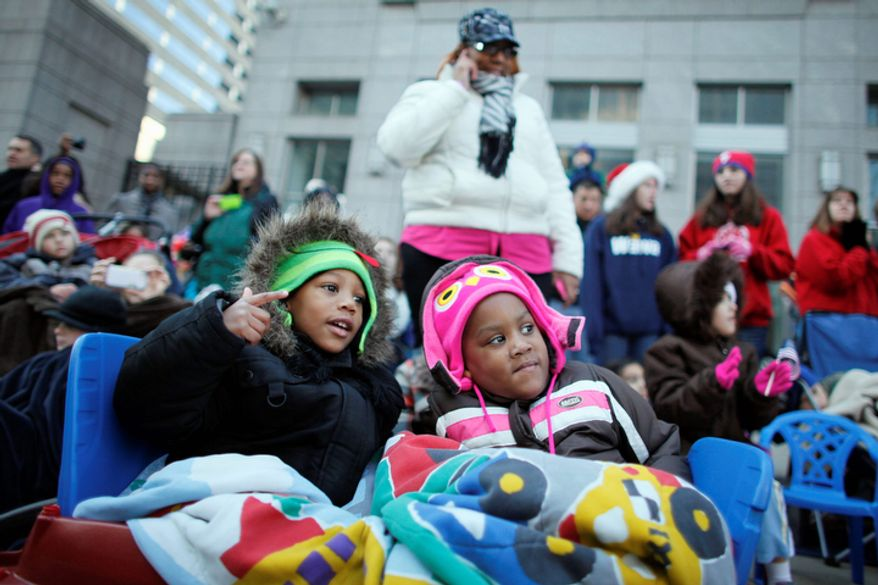 Four year-old twins Kaiden Leach, left, and Kayla Leach watch the 93rd annual Thanksgiving day parade, Thursday Nov 22, 2012, in Philadelphia. New York, Chicago, and Detroit are also among the cities hosting holiday parades. (AP Photo/ Joseph Kaczmarek)