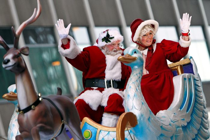 Santa Claus and Mrs. Claus wave to spectators during the 93rd annual Thanksgiving day parade, Thursday Nov. 22, 2012, in Philadelphia.  (AP Photo/ Joseph Kaczmarek)
