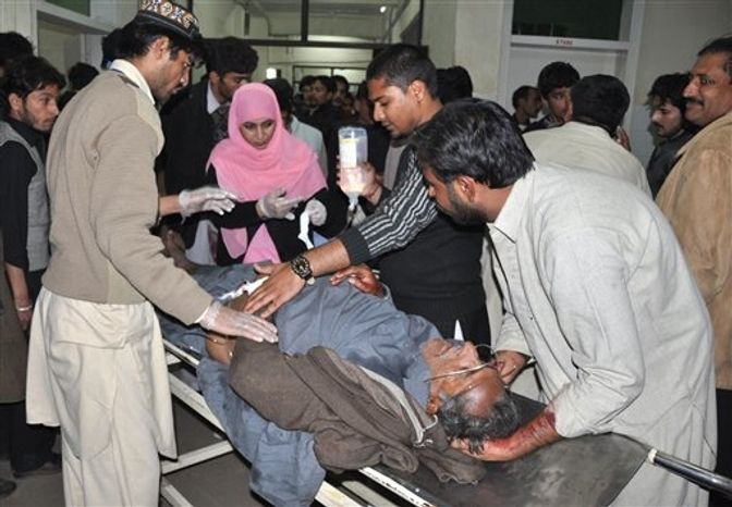 Pakistani hospital staff treat a person injured in a suicide attack on Shiite mourners in Rawalpindi, Pakistan, on Wednesday, Nov. 21, 2