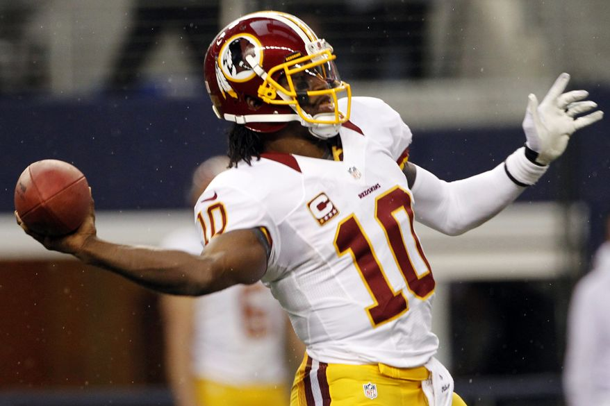 Washington Redskins quarterback Robert Griffin III (10) reaches back to throw a touchdown pass to Aldrick Robinson in the first half of an NFL football game against the Dallas Cowboys, Thursday, Nov. 22, 2012, in Arlington, Texas. (AP Photo/Tim Sharp)