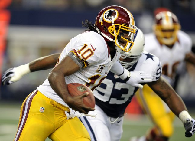 Washington Redskins quarterback Robert Griffin III (10) scrambles out of the pocket as Dallas Cowboys' Anthony Spencer (93) gives chase in the first half of an NFL football game on Thursday, Nov. 22, 2012, in Arlington, Texas. (AP Photo/Matt Strasen)
