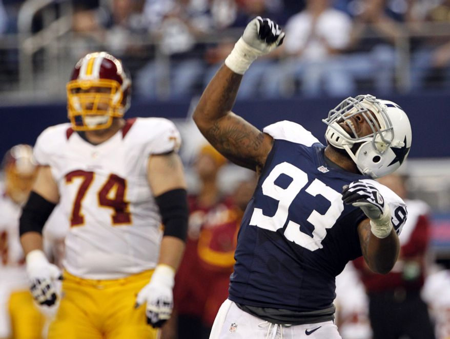 Dallas Cowboys' Anthony Spencer (93) celebrates sacking Washington Redskins quarterback Robert Griffin III, not pictured, as tackle Tyler Polumbus (74) watches in the first half of an NFL football game, Thursday, Nov. 22, 2012, in Arlington, Texas. (AP Photo/Tim Sharp)
