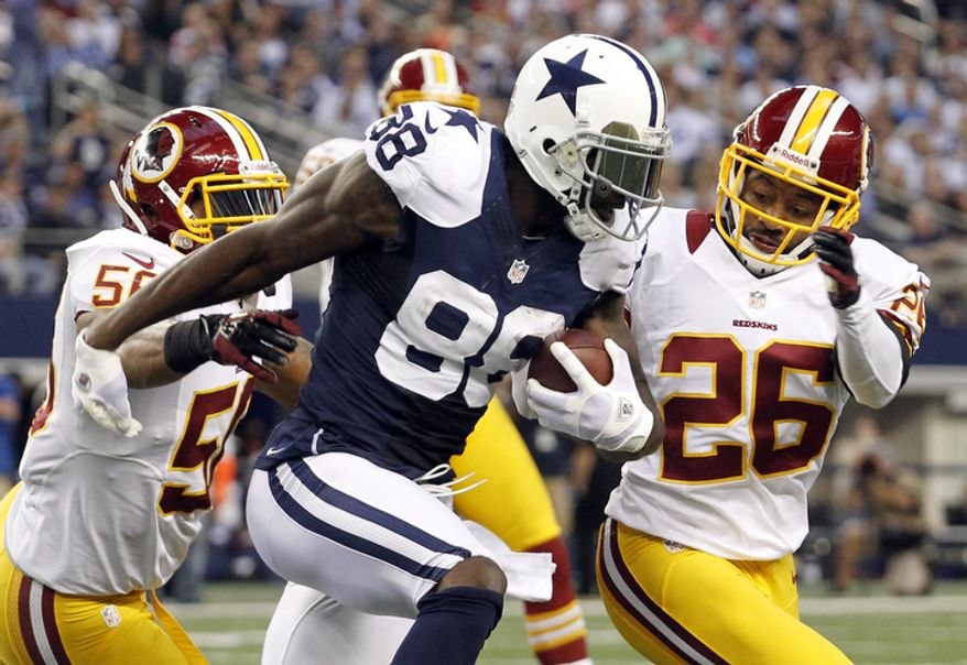 Dallas Cowboys wide receiver Dez Bryant (88) is tackled by Washington Redskins' Perry Riley (56) and Josh Wilson (26) ona short run in the first half of an NFL football game, Thursday, Nov. 22, 2012, in Arlington, Texas. (AP Photo/Tim Sharp)
