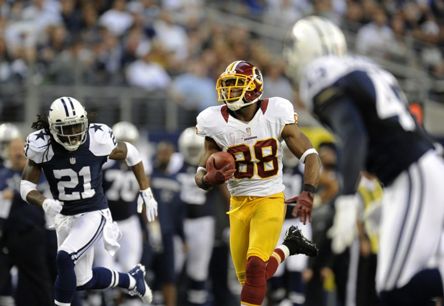 Dallas Cowboys' Mike Jenkins (21) and Gerald Sensabaugh, right, give chase as Washington Redskins wide receiver Pierre Garcon (88) sprints for the end zone and scores in the first half of an NFL football game Thursday, Nov. 22, 2012, in Arlington, Texas. (AP Photo/Matt Strasen)