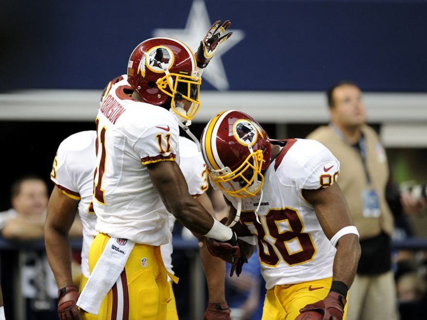 Washington Redskins' Aldrick Robinsonn celebrates his touchdown catch with Pierre Garcon (88) and Darrel Young, rear, in the first half of an NFL football game against the Dallas Cowboys Thursday, Nov. 22, 2012 in Arlington, Texas. (AP Photo/Matt Strasen)