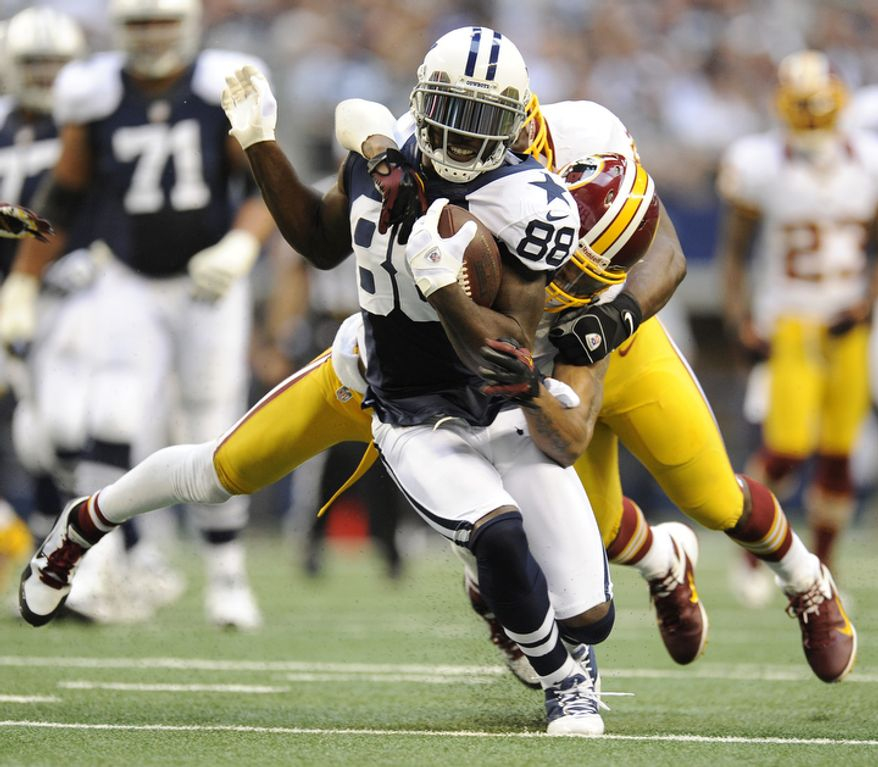 Dallas Cowboys' wide receiver Dez Bryant (88) runs through a tackle attempt by Washington Redskins' Cedric Griffin in the first half of an NFL football game Thursday, Nov. 22, 2012 in Arlington, Texas. (AP Photo/Matt Strasen)