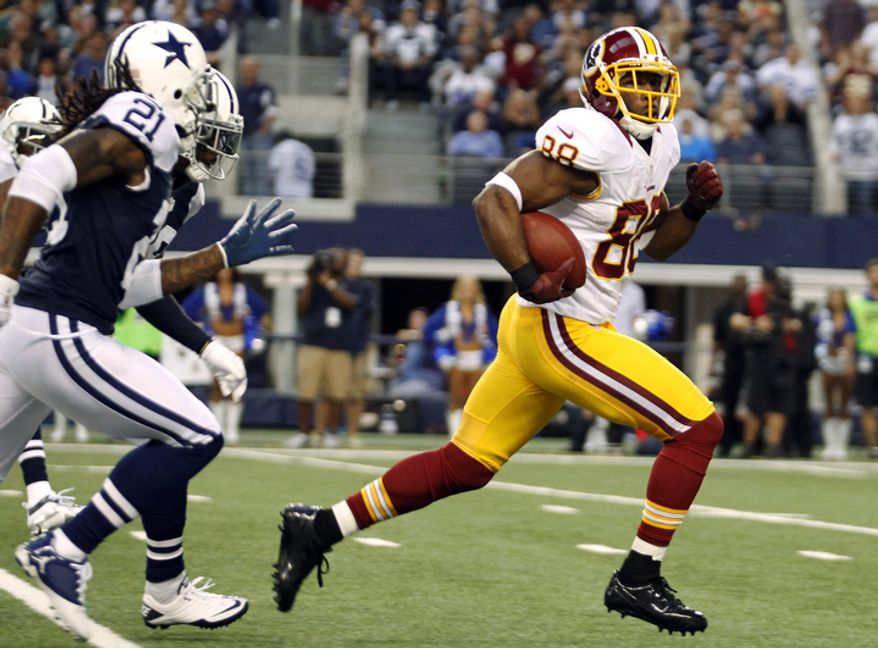 Washington Redskins wide receiver Pierre Garcon (88) looks back at Dallas Cowboys' Mike Jenkins (21) as he sprints for the end zone for a touchdown in the first half of an NFL football game, Thursday, Nov. 22, 2012, in Arlington, Texas. (AP Photo/Tim Sharp)