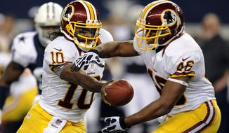 Washington Redskins quarterback Robert Griffin III (10) hands off to running back Alfred Morris in the second half of the Redskins' 38-31 victory over the Dallas Cowboys on Nov. 22, 2012, in Arlington, Texas. (Associated Press)