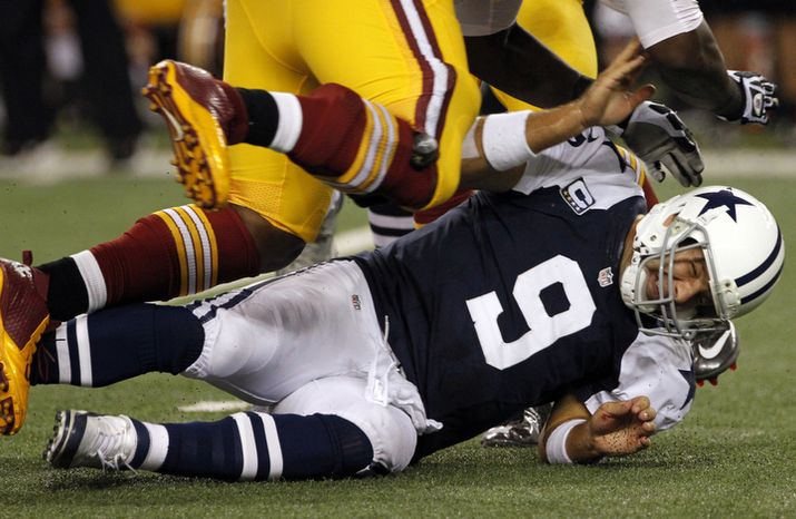 Dallas Cowboys quarterback Tony Romo (9) is knocked to the ground by Washington Redskins' Jarvis Jenkins, top, in the second half of an NFL football game on Thursday, Nov. 22, 2012, in Arlington, Texas. (AP Photo/Tim Sharp)