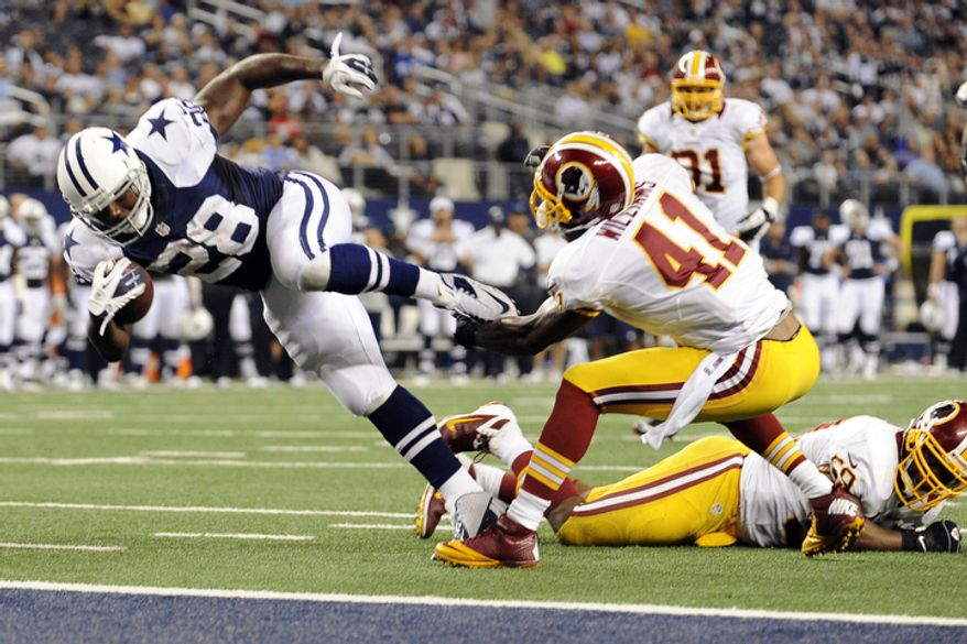 Dallas Cowboys running back Felix Jones (28) leaps into the end zone for a touchdown as Washington Redskins' Madieu Williams (41) attempts the tackle in the second half of an NFL football game, Thursday, Nov. 22, 2012, in Arlington, Texas. Redskins' London Fletcher watches bottom right. (AP Photo/Matt Strasen)