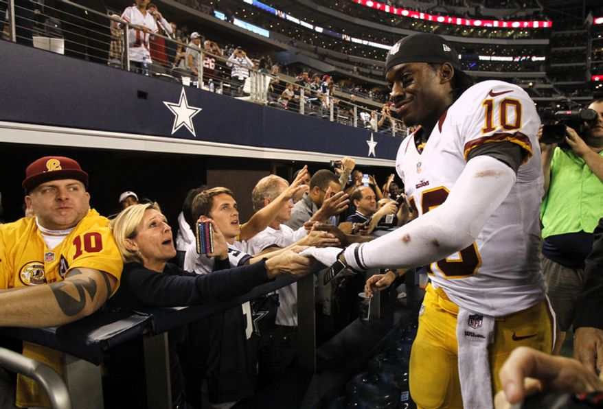 Washington Redskins quarterback Robert Griffin III (10) celebrates with fans following a 38-31 win over the Dallas Cowboys in an NFL football game on Thursday, Nov. 22, 2012, in Arlington, Texas. (AP Photo/Tim Sharp)