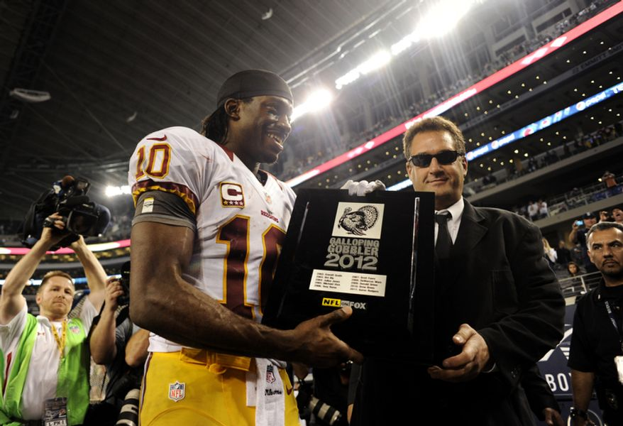 Washington Redskins' Robert Griffin III (10) receives the Galloping Gobbler 2012 award following their NFL football game against the Dallas Cowboys Thursday, Nov. 22, 2012, in Arlington, Texas. The Redskins won 38-31. (AP Photo/Matt Strasen)