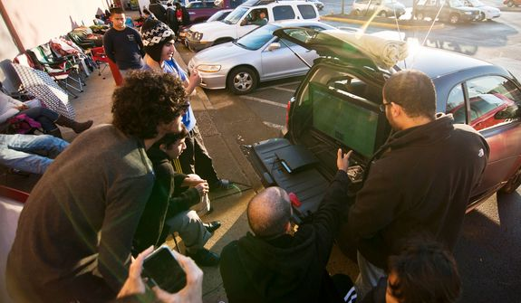 Shoppers play PS3 from a TV powered by their car while they wait in line to be let into Best Buy on Thanksgiving Day, Springfield, Va., Thursday, November 22, 2012.  (Craig Bisacre/The Washington Times)