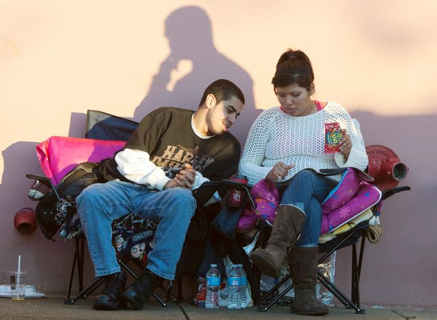 Jesus Marin, 19, from Alexandria, looks over deals with his girlfriend Mariela Paredes, 20, from Fairfax, while wait in line for Best Buy on Thanksgiving Day, Springfield, Va.,