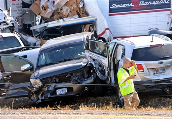 An emergency worker walks past a pile of cars from the accident on Interstate in Southeast Texas Thursday Nov. 22, 2012. The Texas Department of Public Safety says at least 35 people have been injured in a more than 50-vehicle pileup. (AP Photo/The Beaumont Enterprise, Guiseppe Barranco)