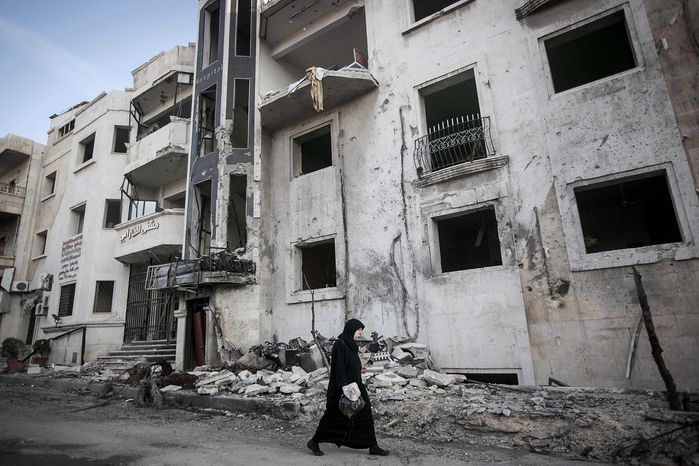 In this Saturday, Nov. 17, 2012, photo, a Syrian woman walks in front of a destroyed hospital where heavy clashes took place between rebel fighters and the Syrian army to seize control over the area, on the outskirts of Aleppo, Syria. (AP Photo/Narciso Contreras)