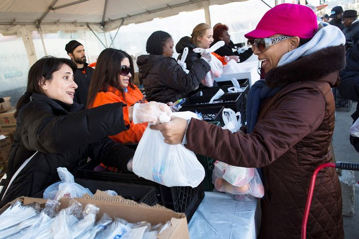Thanksgiving dinners are given out in the Rockaways section of Queens Thursday, Nov. 22, 2012, in New York. The American harvest holiday came as portions of the Northeast still were reeling from Sandy's havoc, and volunteers planned to serve thousands of turkey dinners to people it left homeless or struggling. (AP Photo/John Minchillo)