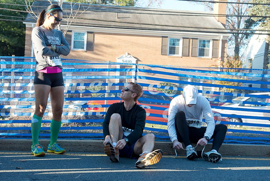 From left, Yoshiko Jo, who got up at 4:30 a.m. to drive from Pennsylvania, David Landau of Potomac, Md. and Daniel Raskas of Silver Spring, Md. prepare to run in the 10k race at the 30th annual Turkey Chase in Bethesda, Md. on Thanksgiving Day, Thursday, Nov. 22, 2012. Ms. Jo and Mr. Landau say this race has become a five-year tradition for them, and it becomes the one day a year the friends see each other. (Barbara L. Salisbury/The Washington Times)