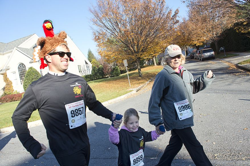 Dad David Thomas, donning a turkey hat, runs with daughter Livie, 5, and grandma Laura Zaletel [cq], all of Washington, D.C., in the two-mile race at the 30th annual Turkey Chase in Bethesda, Md. on Thanksgiving Day, Thursday, Nov. 22, 2012. The event, which raises money for the YMCA, included a 10k race, a two-mile race and a tot trot for the kids. (Barbara L. Salisbury/The Washington Times)