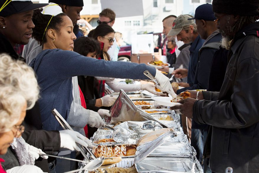 A volunteer serves a free Thanksgiving dinner in the Rockaways section of Queens, Thursday, Nov. 22, 2012, in New York. The American harvest holiday came as portions of the Northeast still were reeling from Sandy's havoc, and volunteers planned to serve thousands of turkey dinners to people it left homeless or struggling. (AP Photo/John Minchillo)