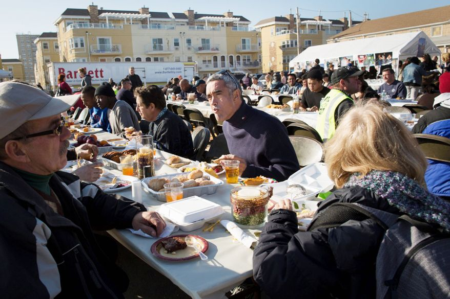Denis Magoolaghan, 67, enjoys a free Thanksgiving dinner in the Rockaways section of Queens, Thursday, Nov. 22, 2012, in New York. The American harvest holiday came as portions of the Northeast still were reeling from Sandy's havoc, and volunteers planned to serve thousands of turkey dinners to people it left homeless or struggling. (AP Photo/John Minchillo)
