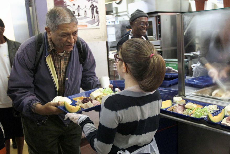 Volunteer Madison Errett, 9, hands out a Thanksgiving meal to a man who wished to remain unidentified at the GLIDE foundation in San Francisco, Thursday, Nov. 22, 2012. GLIDE staff estimated that about 500 volunteers helped prepare and serve around 5,000 meals. (AP Photo/Jeff Chiu)